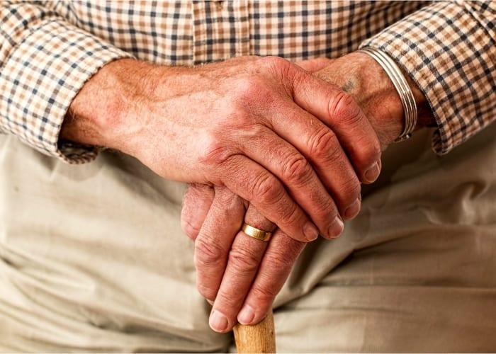 manos cruzadas de una persona mayor que se esta sujetando el baston